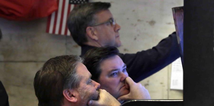 Tres corredores observan con preocupación sus pantallas en el piso de la Bolsa de Valores de Nueva York, (horizontal-x3)
