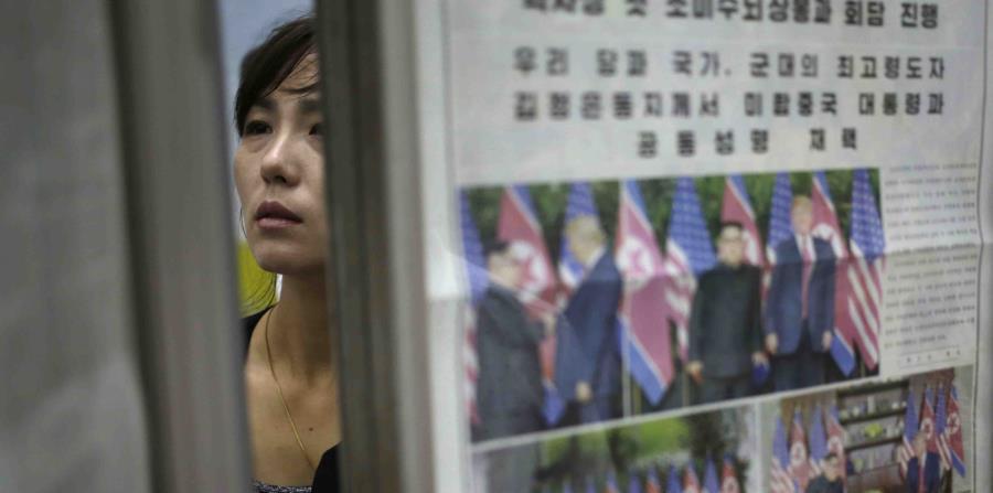 Una mujer norcoreana pasa detrás de un estante de periódicos en los que se reporta la cumbre entre Donald Trump y Kim Jong-un. (AP) (horizontal-x3)