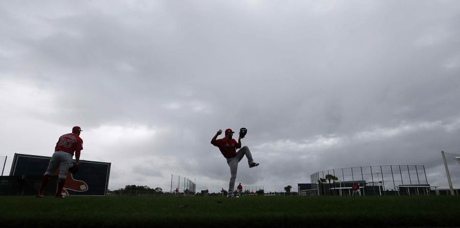 El relevista de los Medias Rojas Brandon Workman, centro, calienta bajo la lluvia durante el primer día de entrenamiento de pretemporada. (AP / Gerald Herbert) (horizontal-x3)