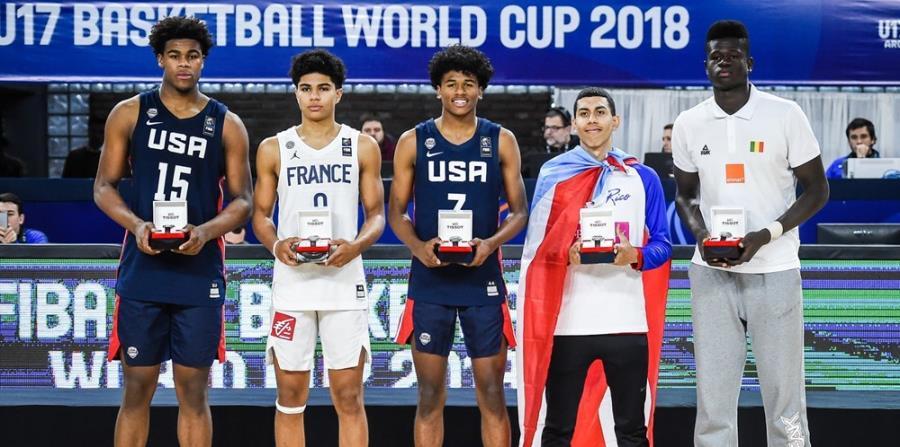 Equipo de estrellas del Mundial Fiba Sub-174 durante la premiación. Arropado con la bandera de Puerto Rico, el armador André Curbelo. (FIBA) (horizontal-x3)