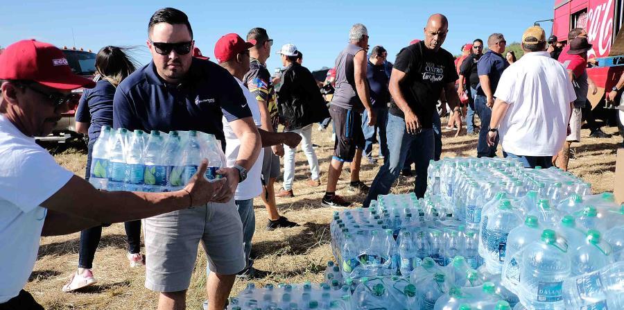Voluntarios de New Fortress Energy ayudan a descargar los abastos de los camiones de Coca Cola. (Suministrada)