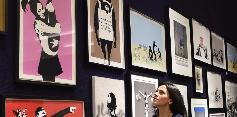 Una empleada de la casa de subastas Bonhams contempla las obras del grafitero británico Bansky, expuestas para los medios en Londres. (EFE) (horizontal-x3)