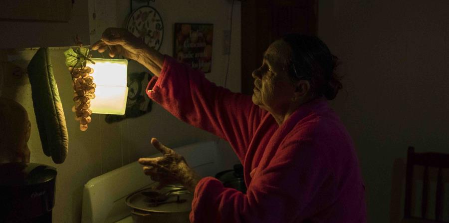 Marta Bermúdez Robles, de 66 años, cuelga una lámpara en su cocina, en Adjuntas, Puerto Rico, ante la falta de electricidad desde el paso de los huracanes Irma y María. (horizontal-x3)