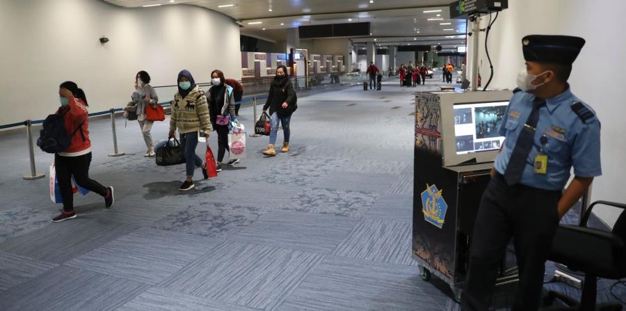 Las autoridades verifican la temperatura corporal de los pasajeros en monitores térmicos, a su llegada al Aeropuerto Soekarno Hatta, en Tangerang, Indonesia. (AP Photo)