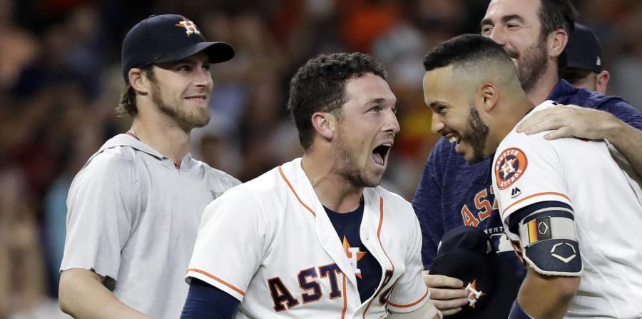 El jugador de los Astros de Houston, Alex Bregman, centro, celebra con Carlos Correa y el resto de sus compañeros luego de conectar un doble productor de dos carreras para darle la victoria a su equipo contra los Rays de Tampa Bay, durante el noveno innin (horizontal-x3)