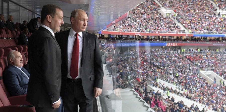 El presidente de Rusia Vladimir Putin, a la derecha, y el primer ministro ruso Dmitry Medvedev, ven el campo durante el duelo entre Rusia y Arabia Saudí que dio inicio al Mundial de fútbol 2018 en el estadio Luzhinski en Moscú, Rusia (horizontal-x3)