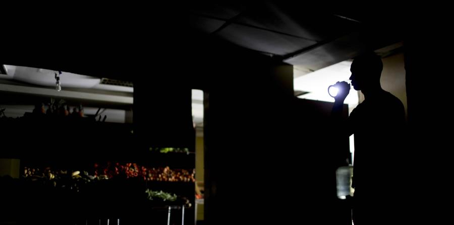 Un hombre alumbra una hilera de un supermercado en Venezuela con una linterna debido a los apagones que agobian al país desde la semana pasada. (AP / Natacha Pisarenko) (horizontal-x3)