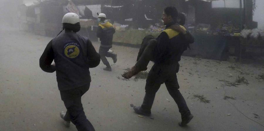 Personal del grupo Defensa Civil Siria, conocido como Cascos Blancos, trasladan a un herido después de los ataques aéreos contra un suburbio en poder de los rebeldes cerca de Damasco, en Siria (horizontal-x3)