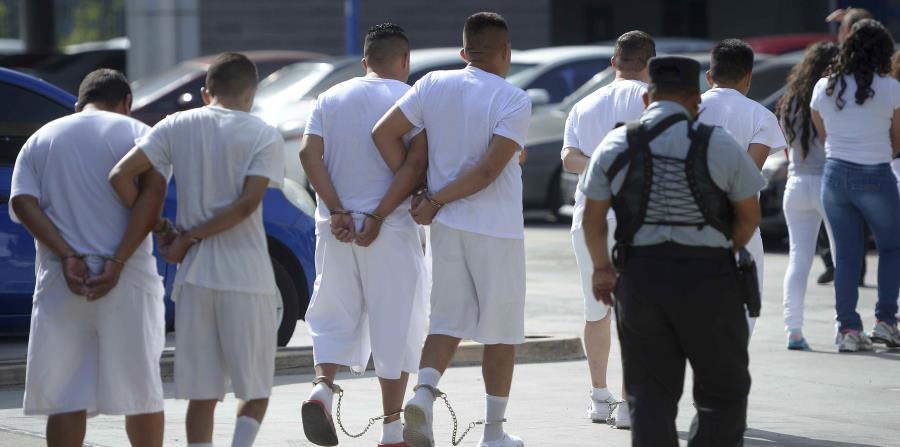 Un grupo de miembros de la pandilla Barrio 18, caminan en fila y con grilletes hacia el Centro de Justicia de San Salvador, (horizontal-x3)