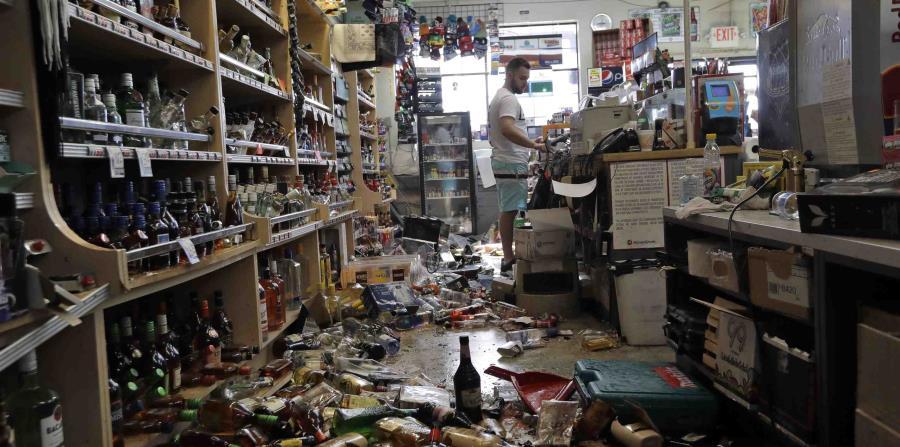 Botellas de licor y otros productos están esparcidos en el piso detrás del mostrador principal del Eastridge Market, el sábado 6 de julio de 2019, en Ridgecrest, California. ( AP/Marcio Jose Sanchez)
