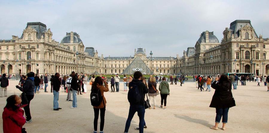 Un grupo de turistas fotografían el Museo del Louvre en París. (EFE/ Juana Benet)