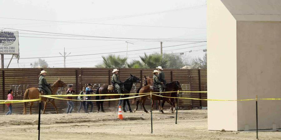 un grupo de personas detenidas por agentes a caballo de la Patrulla Fronteriza tras cruzar de forma ilegal a territorio estadounidense desde Tijuana, México, pasa junto a los prototipos de muro fronterizo, a la derecha, que se están construyendo en San Di (horizontal-x3)