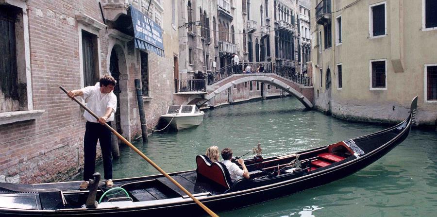 Una pareja de turistas realiza un romántico paseo a bordo de la típica góndola en Venecia. (EFE/nr)