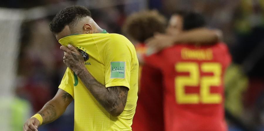 Neymar, de la selección de Brasil, se cubre el rostro con la camiseta mientras los jugadores de Bélgica festejan su triunfo en los cuartos de final de la Copa del Mundo. (AP) (horizontal-x3)