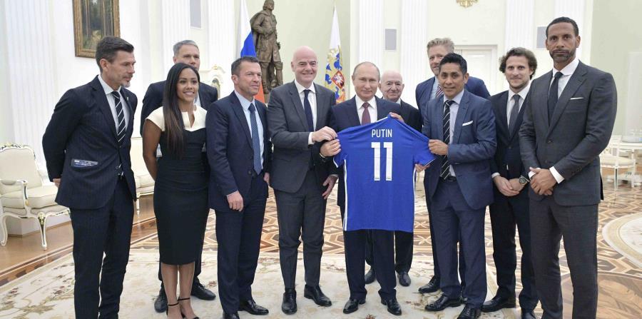 El presidente ruso Vladimir Putin sostiene una camiseta que le obsequiaron, junto al líder de la FIFA Gianni Infantino y varios exfutbolistas, al término de una reunión en el Kremlin. (AP) (horizontal-x3)