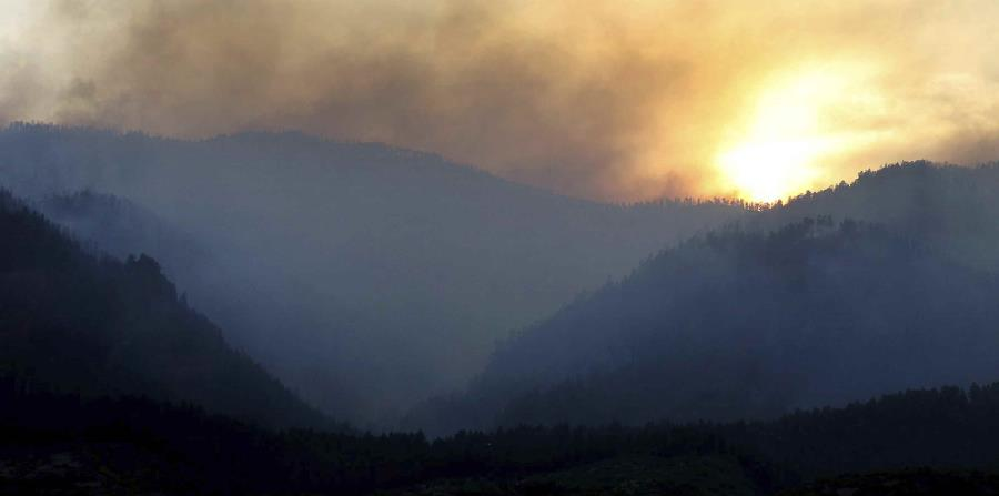 Al ponerse el sol, humo sube de un área incendiada al oeste de la subdivisión Falls Creek Ranch. (horizontal-x3)