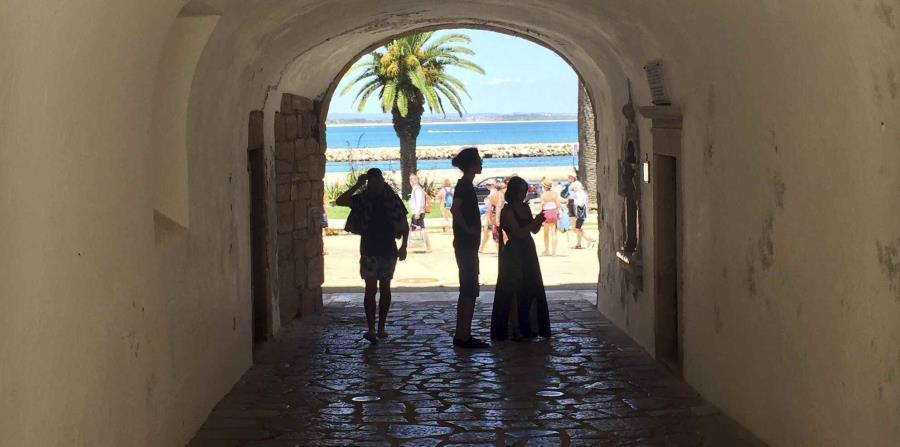 Varios turistas caminan por un túnel en el medieval Castillo de Lagos.