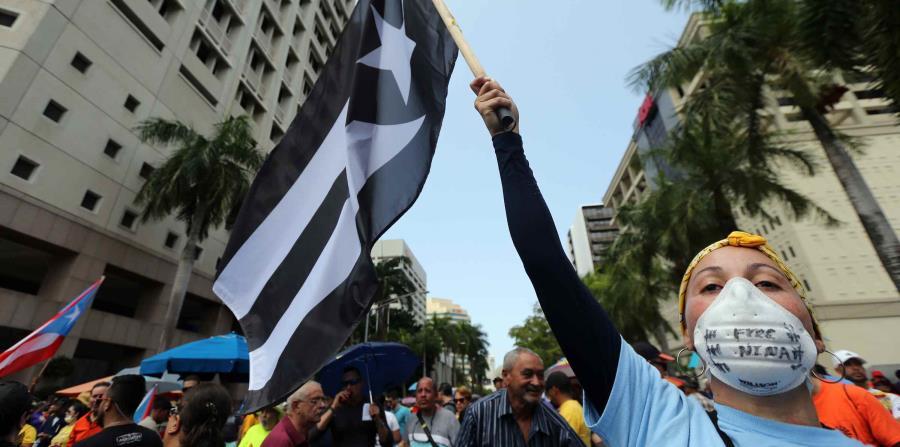 Una mujer levanta una bandera de Puerto Rico con los colores blanco y negro durante una protesta contra la Junta de Supervisión Fiscal. (GFR Media) (horizontal-x3)
