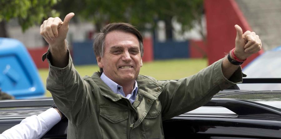 Jair Bolsonaro saluda al público luego de ejercer su voto en la segunda vuelta de las elecciones presidenciales en Brasil. (AP / Silvia Izquierdo) (horizontal-x3)