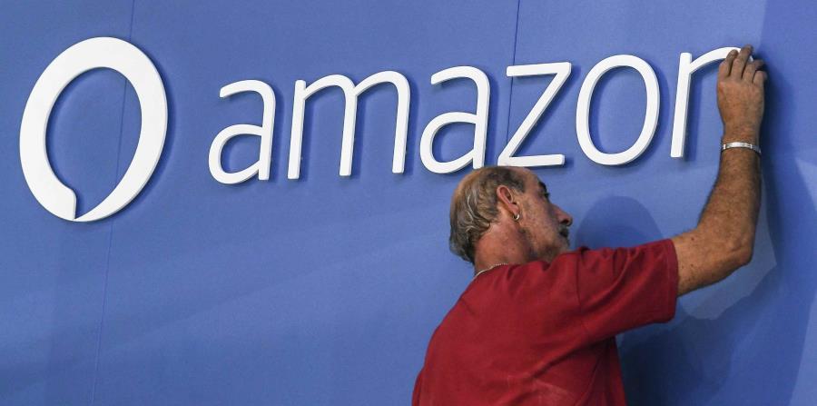 Un trabajador ajusta el logo de Amazon. (EFE) (horizontal-x3)