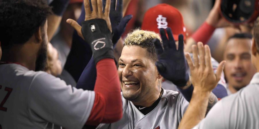 Yadier Molina sonríe mientras es felicitado por sus compañeros de equipo en el dugout. (AP) (horizontal-x3)
