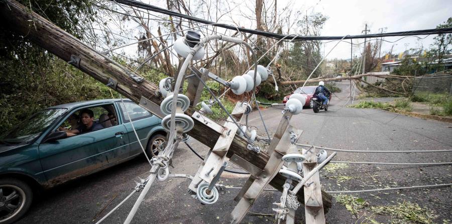 Un conductor pasa debajo de un poste caído en una calle de Mayagüez poco después del paso del huracán María. (GFR Media) (horizontal-x3)