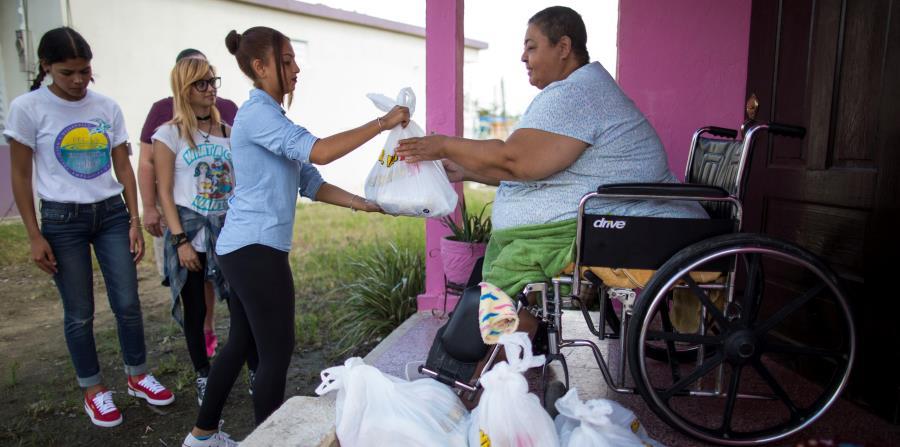 Voluntarios y personal de la organización P.E.C.E.S. le entregan suministros de primera necesidad a una vecina de la calle Del Fuego, en Punta Santiago, Humacao. (Archivo / GFR Media) (horizontal-x3)