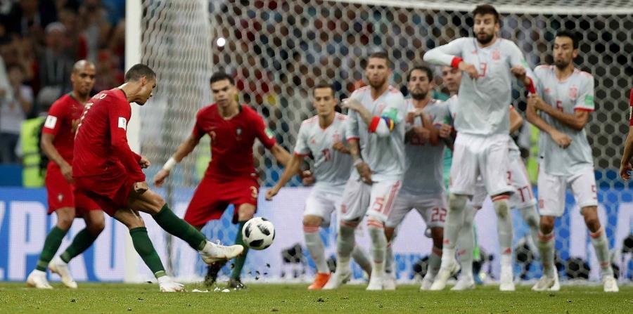 Cristiano Ronaldo ejecutó exquisitamente un tiro libre con el que completó su triplete en el empate de Portugal ante España. (AP) (horizontal-x3)