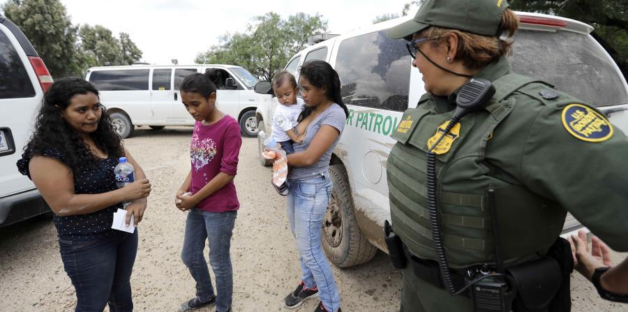 Una agente dialoga con una mujer hondureña que intentaba pasar con sus hijos. (AP) (horizontal-x3)