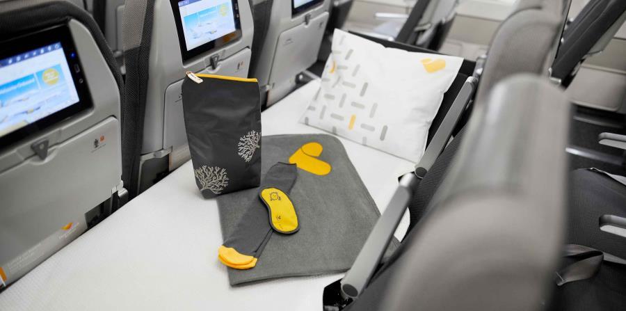 Los usuarios de esta fila de asientos que se convierte en cama tendrá disponible una almohada, una sábana y un kit de amenidades. (Suministrada)