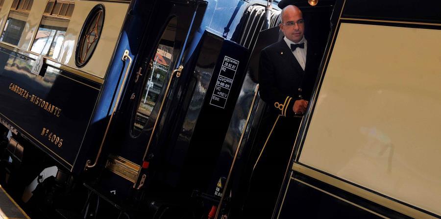 El maquinista del tren Orient Express se asoma a la puerta de uno de los vagones en la estación Smichov de Praga, República Checa. (EFE/Filip Singer )