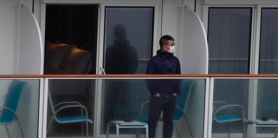 Un pasajero en el balcón del barco World Dream que está anclado en el Hong Kong. (AP)