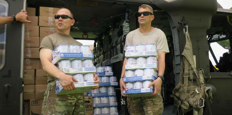 El general Jeffrey Buchanan (derecha) junto a otro militar cargan cajas de comida para bebés en una visita a Jayuya. (horizontal-x3)