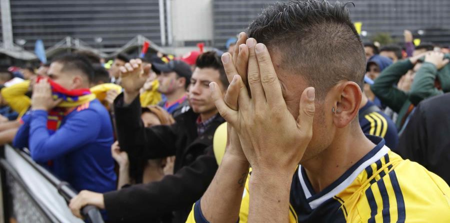 Un aficionado de Colombia se cubre el rostro durante la transmisión del partido entre esa selección sudamericana e Inglaterra en el Mundial de Rusia, en Bogotá. (AP) (horizontal-x3)