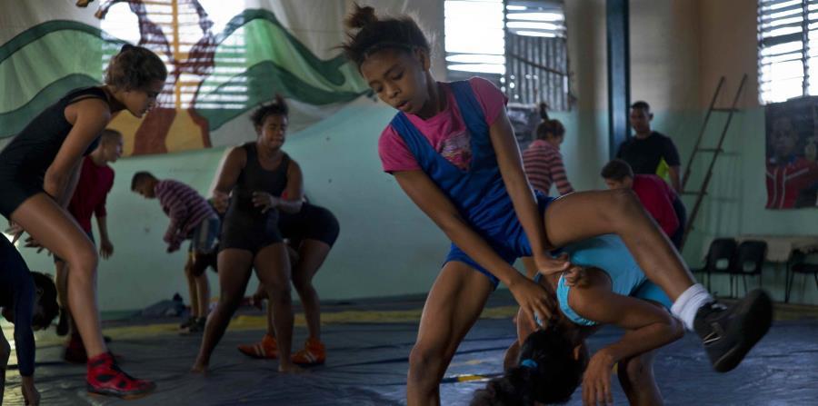 jóvenes luchadoras se entrenan en un gimnasio antes de un torneo amateur organizado por vecinos del vecindario de Chicharrones, en Santiago, Cuba. (horizontal-x3)