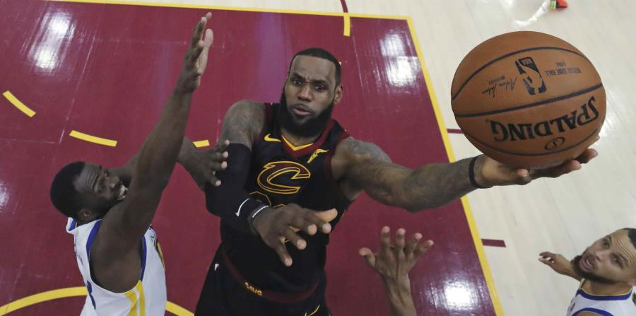 En esta foto de archivo del 6 de junio de 2018, LeBron James, de los Cavaliers de Cleveland, hace un tiro sobre Draymond Green durante el tercer juego de la final de la NBA, en Cleveland. (AP) (horizontal-x3)