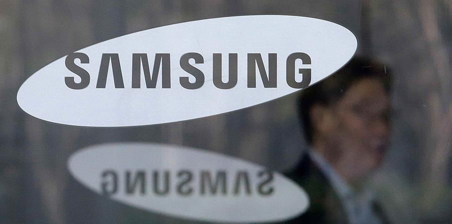 Un empleado camina detrás de un logo de la compañía Samsung. (AP) (horizontal-x3)