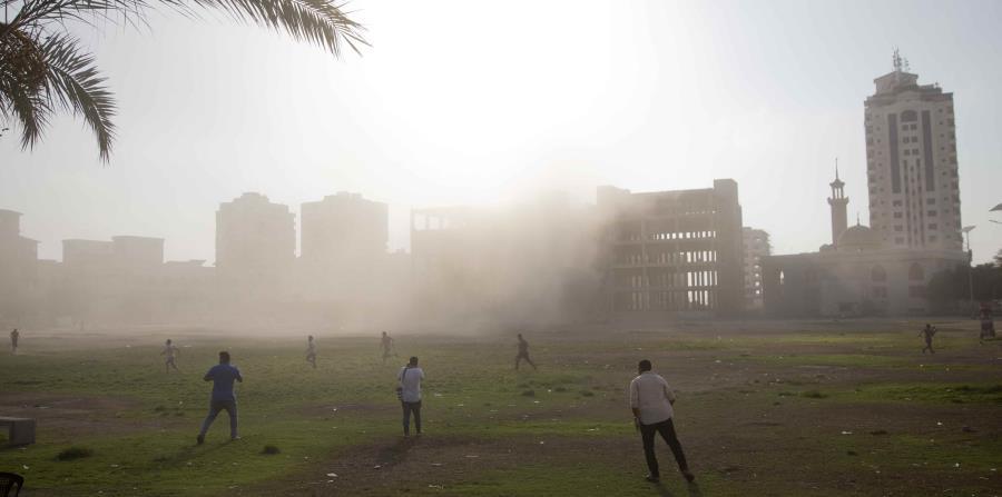 Palestinos se apuran para revisar una zona atacada en una operación aérea israelí contra un edificio gubernamental (horizontal-x3)