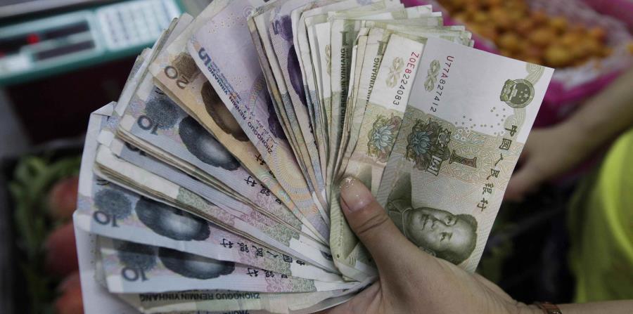 Una vendedora muestra billetes de yuan en Pekín, China. (horizontal-x3)