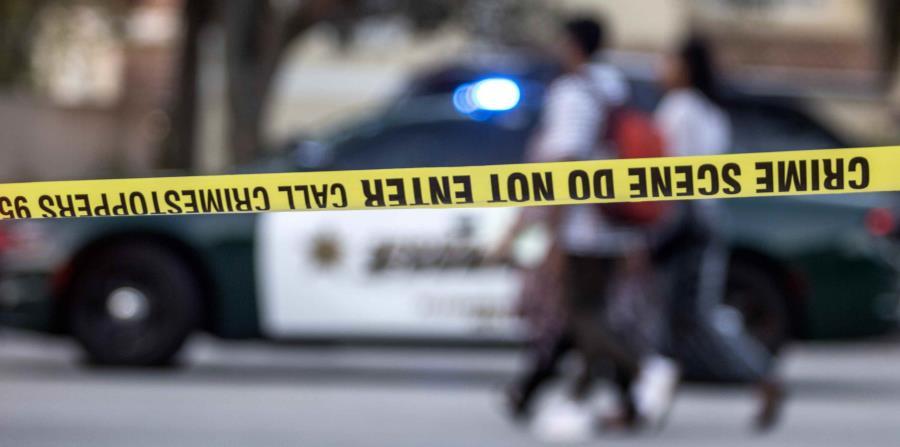 Un grupo de personas camina frente a la zona acordonada tras el tiroteo registrado hoy, miércoles 14 de febrero de 2018, en la escuela secundaria Marjory Stoneman Douglas de la ciudad de Parkland (horizontal-x3)