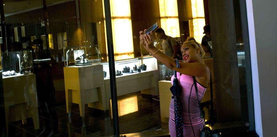 Adolescentes y jóvenes adultos posan para fotos que publicarán en Facebook frente a las vidrieras de los negocios, haciendo gestos de la victoria ante imágenes que repiten las que les envían sus familiares desde Miami (horizontal-x3)