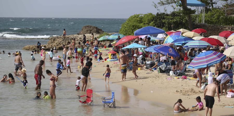 Cientos de personas se dieron cita a la playa del Último Trolley para darse un chapuzón. (horizontal-x3)