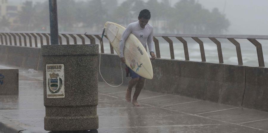 Un surfer corre por una acera mientras llueve. (GFR Media) (horizontal-x3)