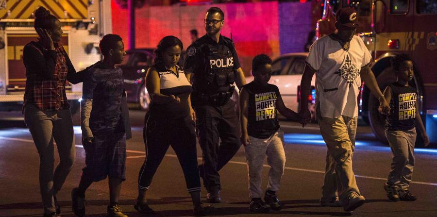 La Policía desaloja a una familia del lugar de la balacera. (AP) (horizontal-x3)