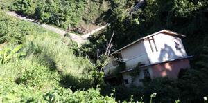 Así permanece la casa que se fue por un barranco en Corozal