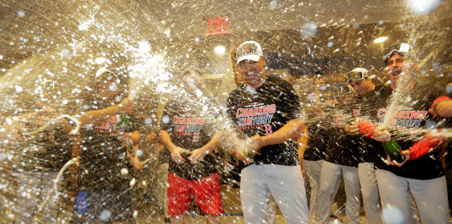 El dirigente de los Medias Rojas, Alex Cora, se une a la celebración de su equipo en el camerino del Yankee Stadium. (AP / Frank Franklin II) (horizontal-x3)