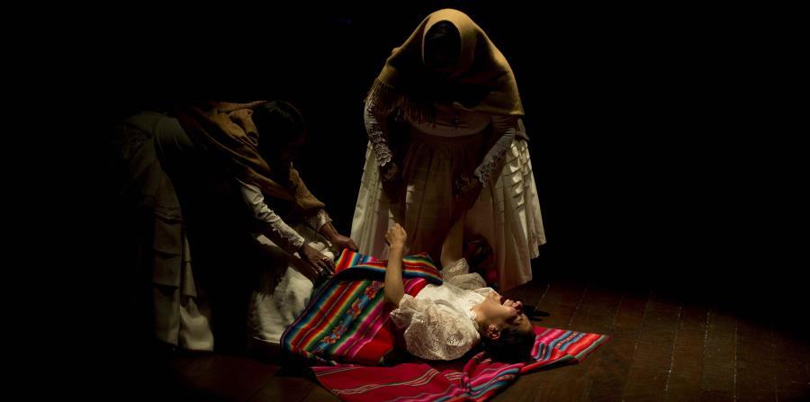 En esta imagen del 30 de abri de 2019, el foco ilumina a un grupo de mujeres comerciantes reconvertidas en actrices, que narran historias sobre la violencia de género en el Teatro Municipal de La Paz, Bolivia. (AP/Juan Karita)