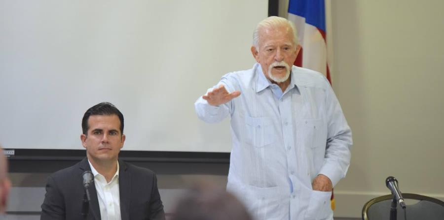 El exgobernador Carlos Romero Barceló (de pie) junto al gobernador Ricardo Rosselló durante una reunión de la Comisión de Igualdad en Miami. (horizontal-x3)