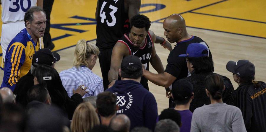 Kyle Lowry se queja con uno de los árbitros luego de ser empujado por el inversionista de los Warriors, Mark Stevens, durante el tercer choque de la serie final de la NBA. (AP / Tony Avelar) (horizontal-x3)
