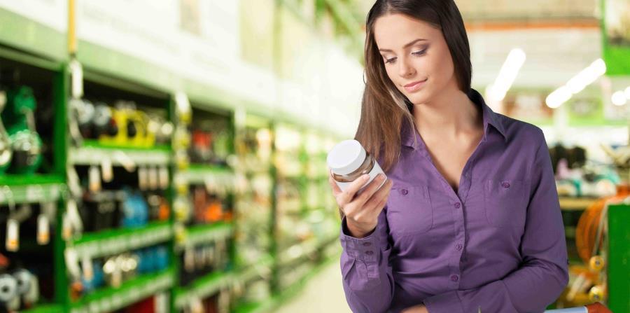Mujer en colmado leyendo etiqueta nutricional. (horizontal-x3)